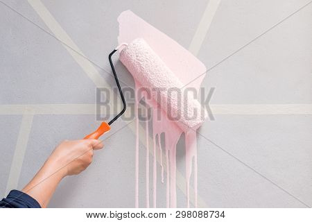 Young Woman With The Roller Painting The Wall In New House.