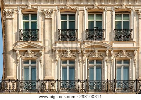 Facade Of One Of The Beautiful Buildings Along Champs Elysees Avenue With Typical Wrought Iron Fence
