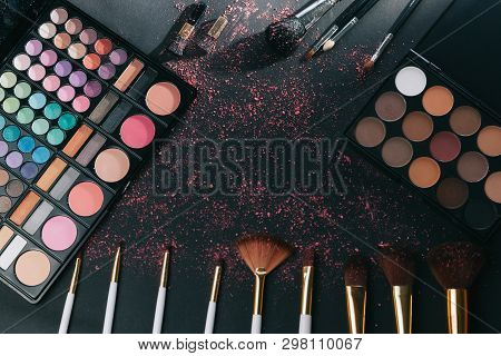 Makeup Brushes And Eye Shadow On Black Background.