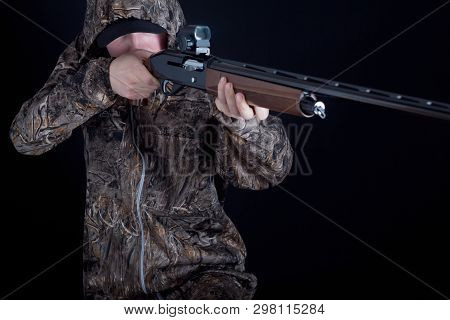 Hunter In Camouflage Clothing With A Gun On A Black Background Isolated. The Man With The Shotgun. Y