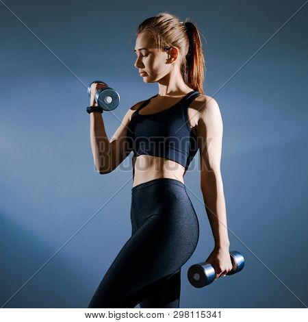 Portrait of Young Attractive Sports Woman Lifting Dumbbells in the Gym. Fitness and Healthy Lifestyle Concept.