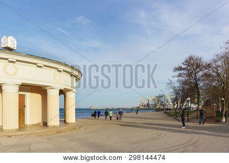 Feodosia, Crimea, Russia - March 08, 2019: People Walk On The Waterfront Near The Cargo Port In Feod