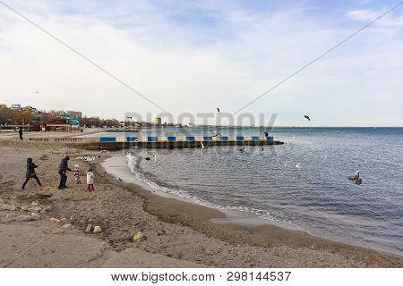Feodosia, Crimea, Russia - March 08, 2019: People On The Black Sea Coast In Feodosia. Spring Day. Of