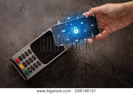 Hand paying with cellphone on POS, secure payment concept