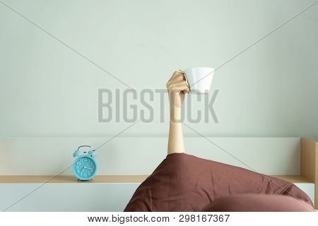Woman Showing Arm Raised Up Holding Coffee Cup On Bed Under Duvet In The Bed Room, Young Girl With H