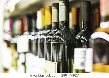 Close Up Row Of Wine Bottles In Wine Store Or In Supermarket Shop Shelf Shallow Dof