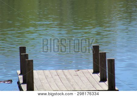 Greenish Water At The End Of A Wooden Dock On The Lake At Vastwood Park In Hawesville, Kentucky.