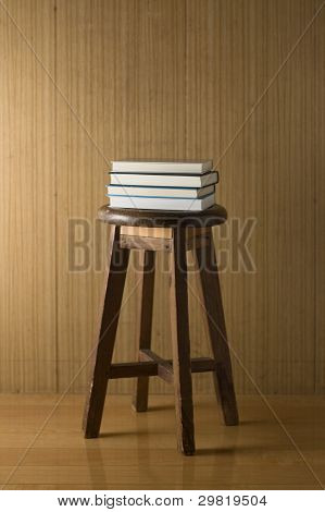 Old chair and books with wooden wall.