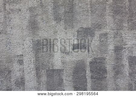 Gray Granular Concrete Wall With Dark Streaks Of Paint And White Spots. Rough Surface Texture