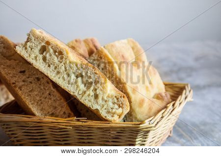 Italian Bread Of Focaccia Genovese Type On Display On A Basket On A Wooden Table, Sliced In Squared