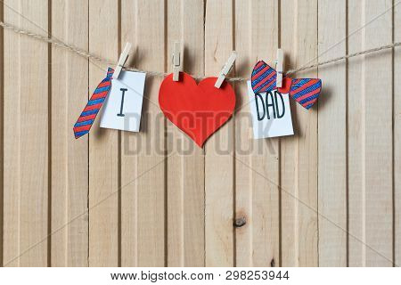 Fathers Day Concept. Message With Paper Hearts, Tie And Bow-tie Hanging With Pins Over Light Wooden