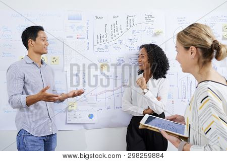Smilng Vietnamese Businesswoman Talking To Colleagues In Front Of Wall Covered With Various Charts A
