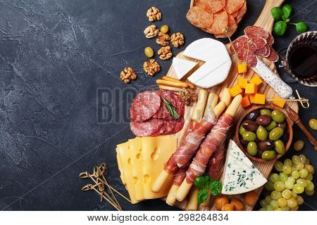 Italian Appetizers Or Antipasto Set With Gourmet Food On Black Kitchen Table Top View. Mixed Delicat