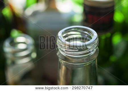 Glass Bottle Neck and Finish known as Small Mouth External Thread, Screw Threads,  Screw-Top, Screw-Cap, Helix, Coil, Duplex and External Screw Thread. Blurred Glass Bottles Background. poster