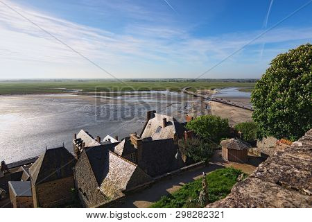 Battle Between Water And Land. High Tide Water Is Going To The Bridge Between Mont Saint-michel Abbe