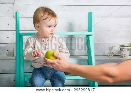 A Little Boy Does Not Want To Take An Apple From A Stranger. He Looks Incredulous And Sits On The St