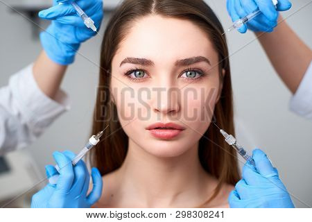 Hands Of Beauticians Holding Syringes Around Flawless Woman Face Ready For Injection In Cosmetology