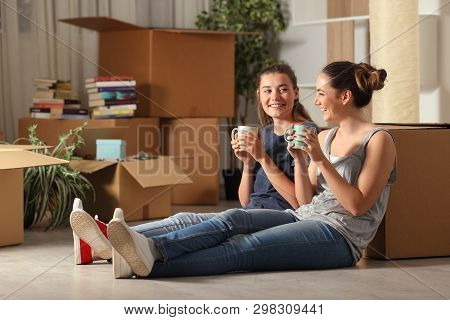 Two Happy Roommates Moving Home Resting And Talking Sitting On The Floor In The Night