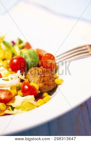 Colorful Fresh Vegetable Salad With Meatballs And Corn Seeds On Rustic Background. Copy Space