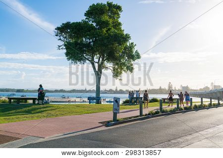 People Enjoying The Sunny Weather On The Waterside In The City Of Forster, A Coastal Town In The Gre
