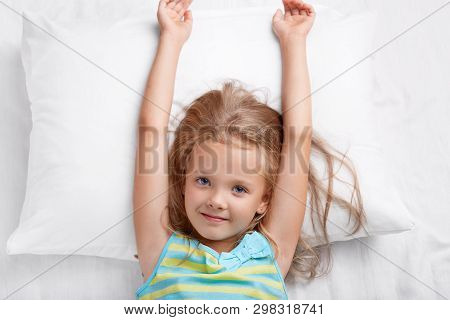 Top View Of Pretty Child Has Long Hair, Stretches In Bed, Lies On White Pillow, Has Good Mood After
