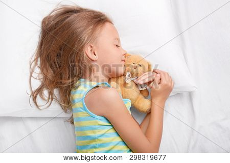 Restful Female Child With Light Messy Hairstyle, Lies On Side, Keeps Her Favourite Teddy Bear In Han