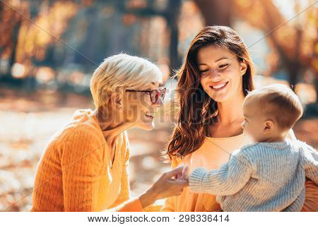 Grandmother And Mother Smiling At Baby In Autumn Park.