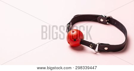 Red Ball gag on pink background. Intimate toys. Sex abuse slavery. Copy space for text poster