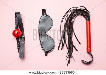 Set of erotic toys for BDSM. The game of sexual slavery with a whip, gag and leather blindfold. Intimate games poster