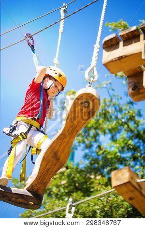 Little Brave Caucasian Girl At Outdoor Treetop Climbing Adventure Park