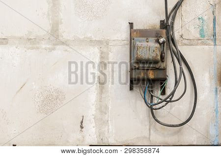 Old Rusty Unkempt Electric Shield With A Switch On The Wall Of An Industrial Building Made Of Concre