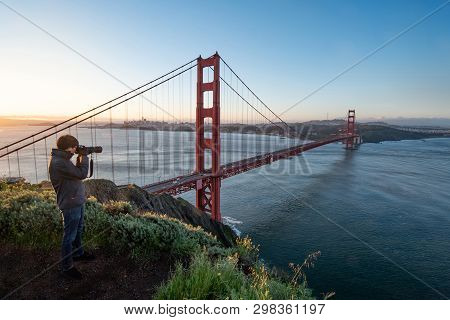 Asian Man Photographer And Tourist Enjoy Taking Photo Of Golden Gate Bridge During Sunrise, Iconic B