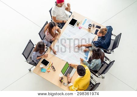 Top view scene of Asian and Multiethnic Business people with casual suit working with brainstorming and pointing to the design concept in the modern workplace, people business group concept