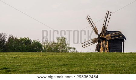 Wooden Windmill On The Hillside Against A Background Of Trees And Blue Sky. Selective Focus.