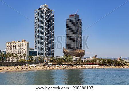 Spain, Barcelona, March, 08, 2019 - Sandy   Barceloneta Beach Near The Port Of Olympic On The Backgr