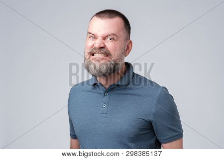 Mature Man Angry And Aggressively Bares His Teeth.