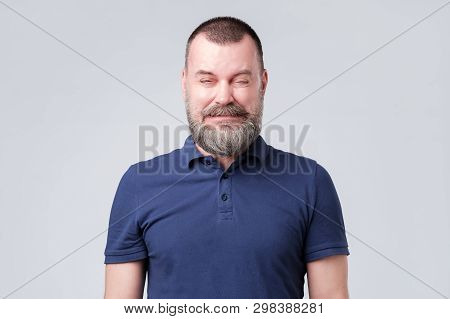 Mature Man In Blue Shirt Wrinkled Due To Sour Taste.
