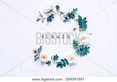Summer flower background with composition made of white rose flowers and Summer inscription on the white background. Flat lay, top view