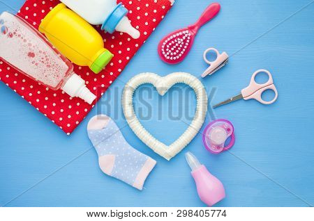 Newborn baby story. Childrens toys, scissors, baby bottle, nipple, hairbrush on red background poster