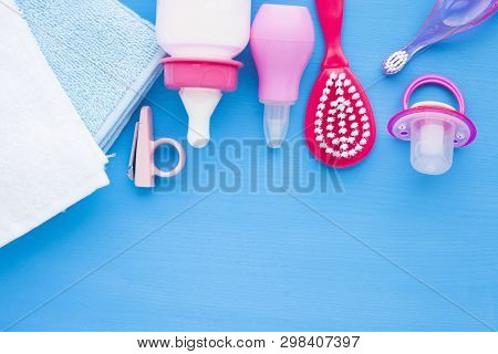 Newborn baby story. Towels and childrens toys, scissors, baby bottle, nipple, hairbrush on blue background poster