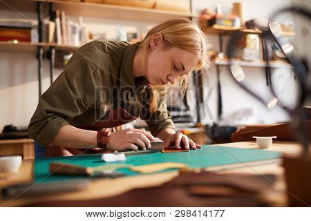 Warm toned portrait of female artisan  tracing leather patterns while working in shoemaking atelier, copy space poster