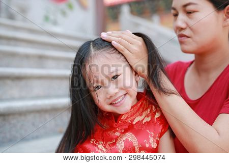 Portrait Of Mother Tying Her Daughter's Hair. Two Tied Ponytails Hairs. Child Girl Looking At Camera