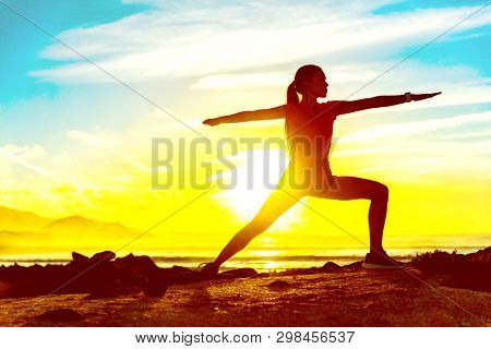 Yoga well-being woman training outdoors in morning sunrise. Wellness and health concept. Silhouette againts sun sky.