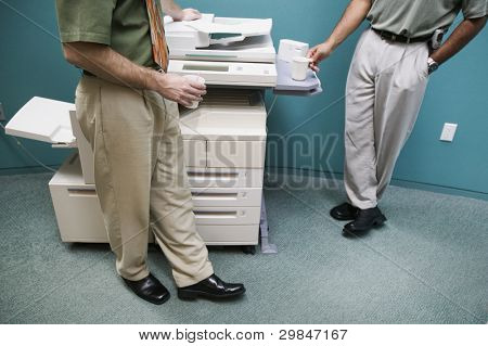 Low section of two businessmen at copy machine