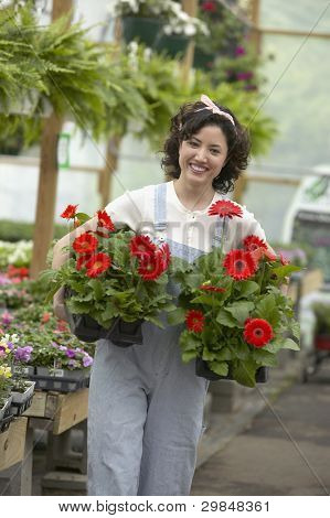 Young woman carrying potted flowers