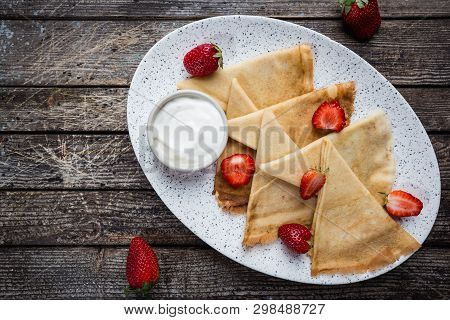 Crepes With Strawberry And Cream Sauce. Homemade Thin Crepes For Breakfast Or Dessert On Wooden Back