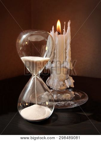 Still Life With Vintage Sandglass And Burning Candle Against A Low Key Background. Selective And Sof