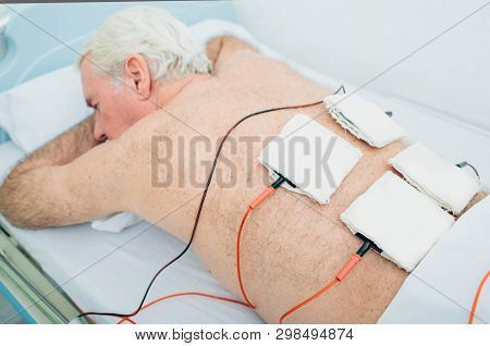 Physiotherapeutic Treatment. Senior Patient Having Ultrasound And Electrotherapy Treatment On His Ba