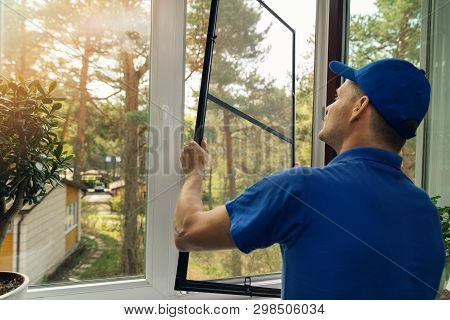 Worker Installing Mosquito Net Wire Screen On House Window