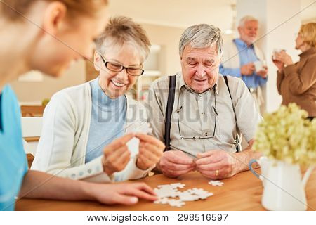 Seniors with Alzheimer's disease or dementia playing puzzle with senior care